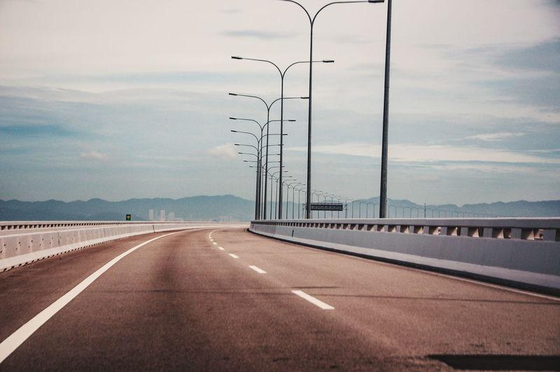 Row of street lights on bridge against sky