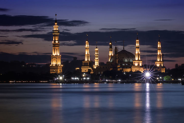 Illuminated mosque by river against sky at night