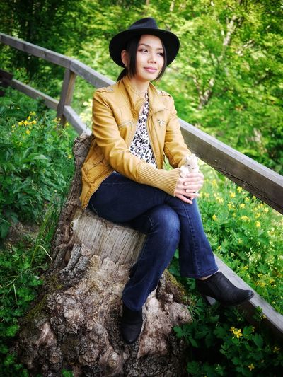 Beautiful young woman sitting on tree stump in forest