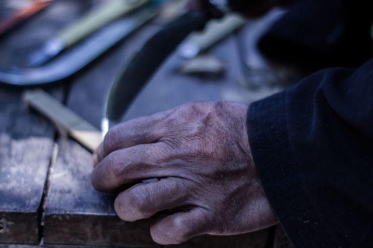 Close-up of man working on table in workshop
