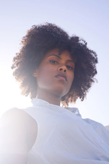 Low angle muted colors portrait of a young black woman with afro hair