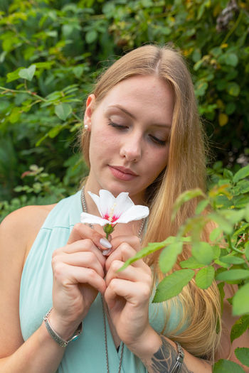 Young woman holding flower while standing against plant