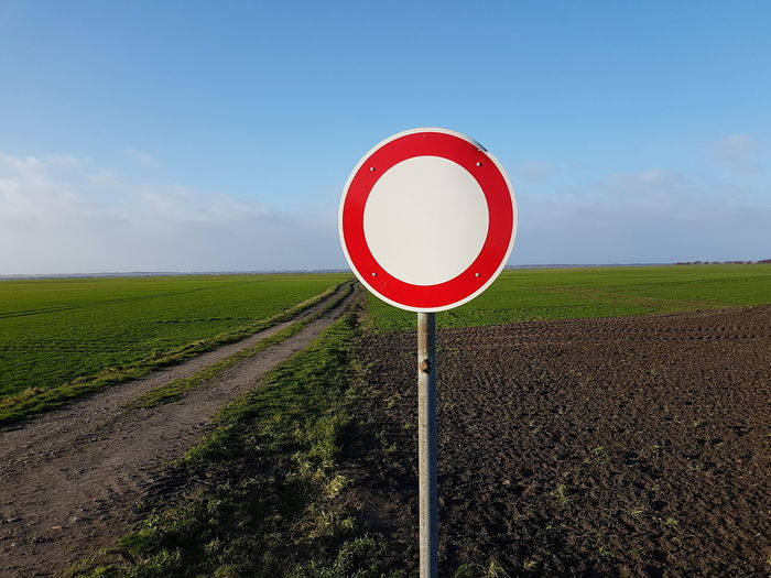 Road sign on field against sky