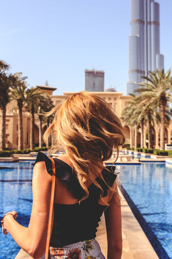 Rear View Of Woman Standing By Swimming Pool In City