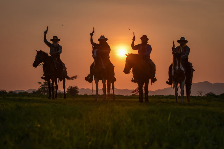Silhouette people riding on field against sky during sunset
