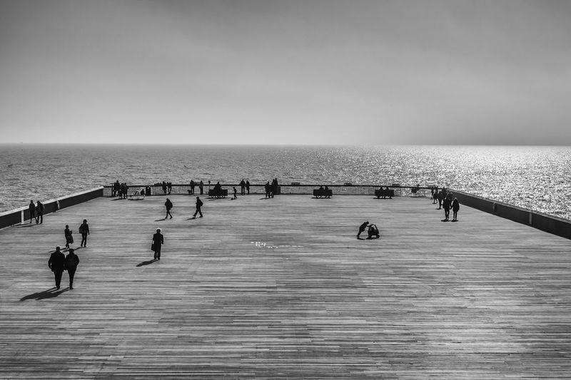 People on promenade by sea against sky