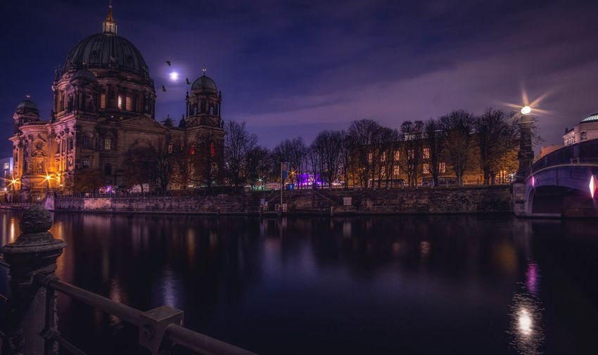 River by berlin cathedral in illuminated city at night