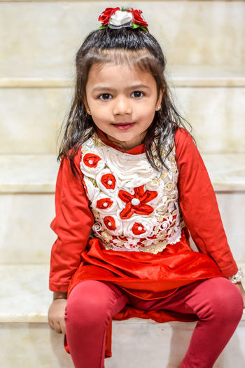 Portrait Child Childhood Smiling Girls Happiness Red Looking At Camera Friendship Cute Toddler  18-23 Months Gap Toothed Baby Clothing One Baby Girl Only Babyhood Warm Clothing Preschooler Preschool Age Tobogganing Single Parent 12-23 Months Baby Babies Only