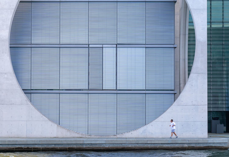 Man Jogging By Modern Building In City