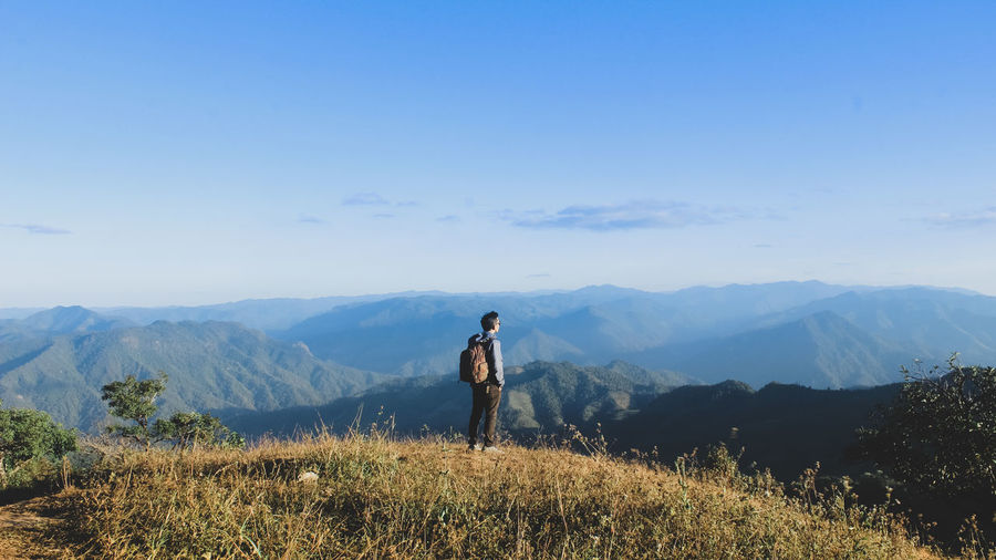 Man on top mountain view. Life style concept. Beauty In Nature Day Environment Holiday Idyllic Landscape Leisure Activity Lifestyles Looking At View Mountain Mountain Range Nature Non-urban Scene One Person Outdoors Real People Scenics - Nature Sky Standing Tranquil Scene Tranquility Trip