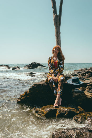 Portrait of woman sitting on rock by sea against clear sky