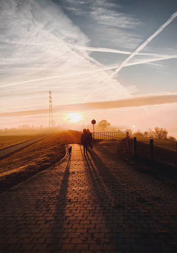 Man on railroad track against sky during sunset