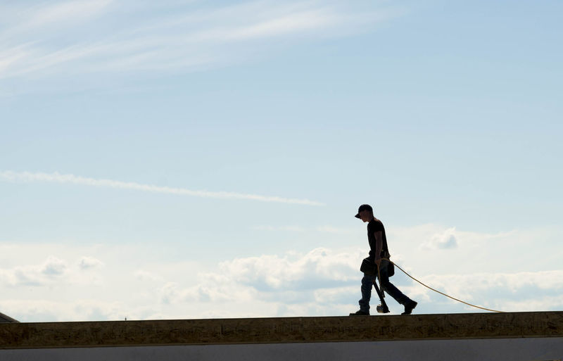 Side view of man walking against sky
