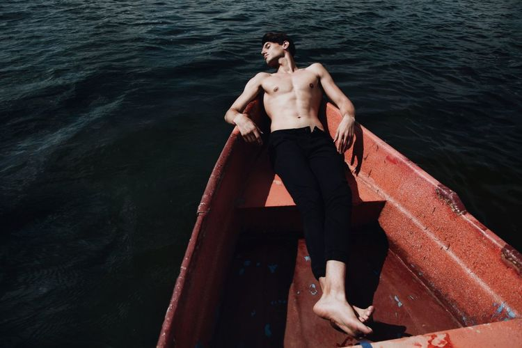 High Angle View Of Young Man Sleeping In Boat On Lake