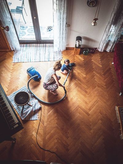 High angle view of man sitting on hardwood floor at home