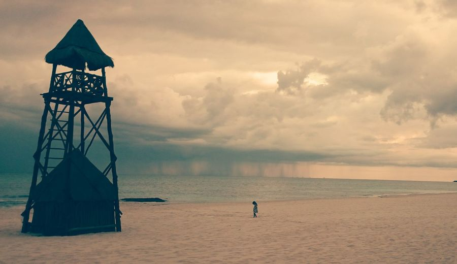 Lookout Tower At Sea Shore Against Cloudy Sky During Sunset