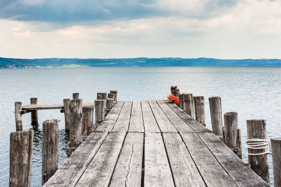 Jetty pier on lake in winter cloudy day Day Jetty Lake Nature One Person Only Men Outdoors Pier Scenic Scenics Sea Sky Travel Water Winter Wood - Material