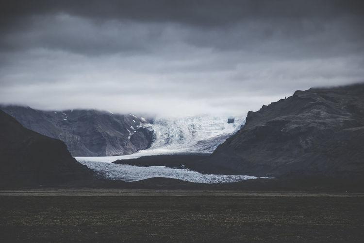 A glacier appears during the scenic drive to Jökülsarlon glacier like in Iceland. Area Dark Frozen Ice Nature Travel Winter Backpack Blue Brown Frozen Water Glacier Grey Landscape Moody Mountain Rocks Sky Snow Volcano
