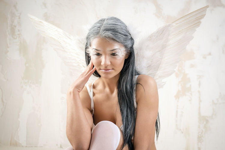 Young woman as angel with white wings over white obsolete wall Fairy Makeup Myth Pensive Portrait Of A Woman Wall Woman Angel Angel Wings Attractive Beautiful Woman Beauty Brunette Indoors  Lingerie Long Hair Model Mythology One Person Pose Sexygirl Studio Shot Underwear😈 Young Adult Young Women