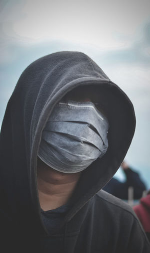 Close-up of man covering face with surgical mask