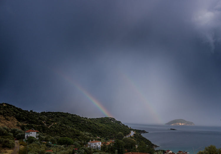 Scenic view of rainbow over mountains against sky