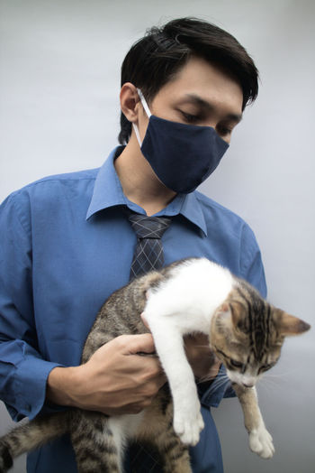 Portrait of doctor wearing mask holding cat against wall