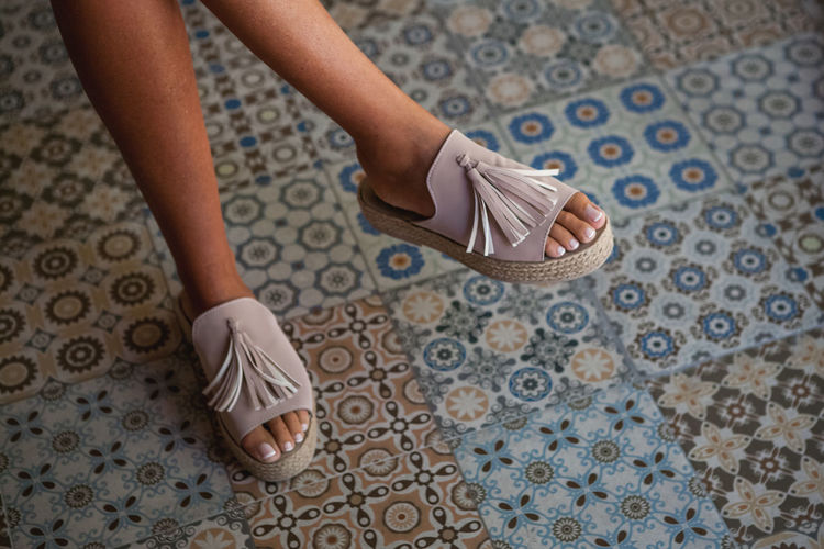 Low Section Of Woman Sitting Over Tiled Floor