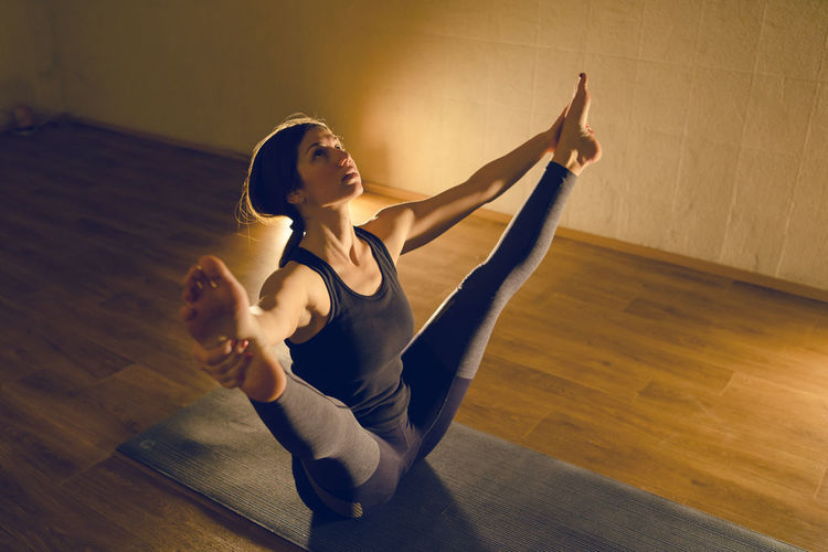 High angle view of woman doing yoga while sitting on floor