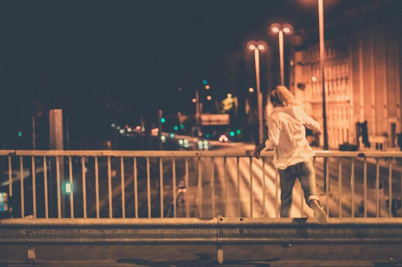 Rear view of woman walking on illuminated bridge at night