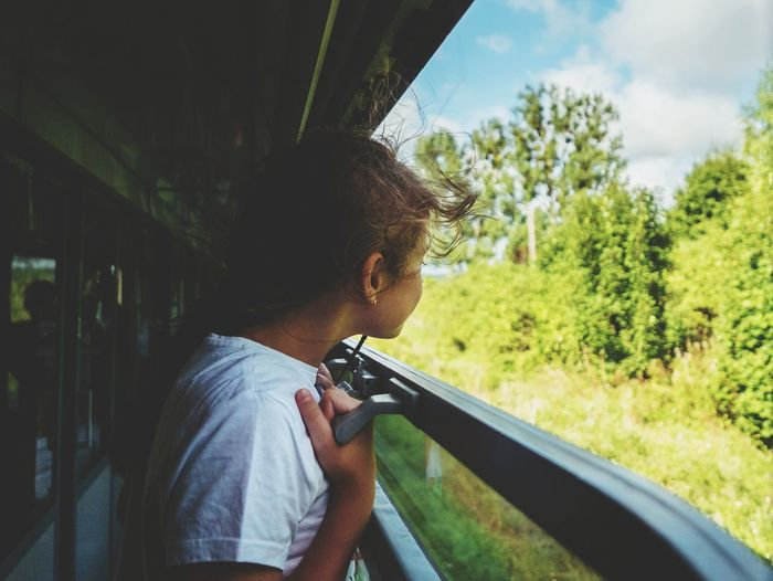 Side View Of Girl Looking Through Train Window