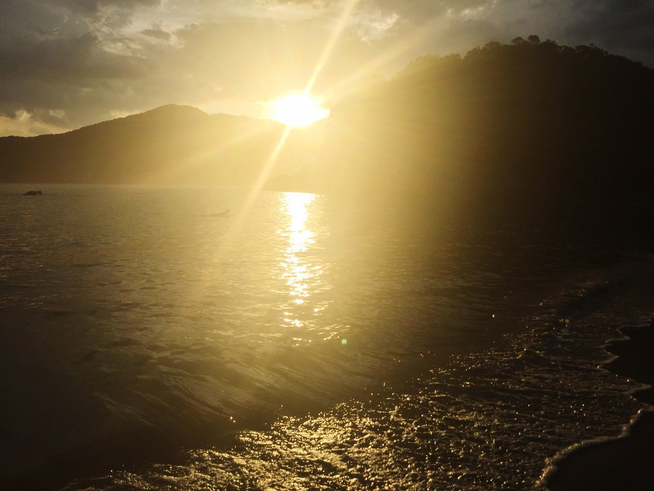 sunset, sun, sunbeam, sunlight, lens flare, nature, beauty in nature, water, scenics, tranquil scene, tranquility, silhouette, reflection, outdoors, no people, idyllic, sky, mountain, sea, travel destinations, vacations, day