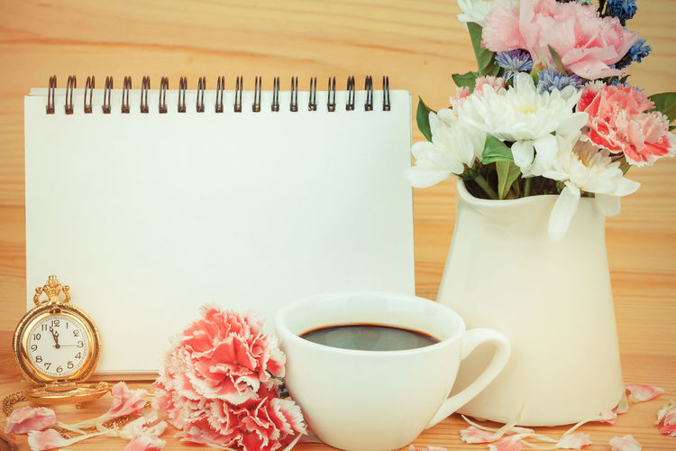 Close-up of coffee cup with flower vase and spiral notebook against wooden wall