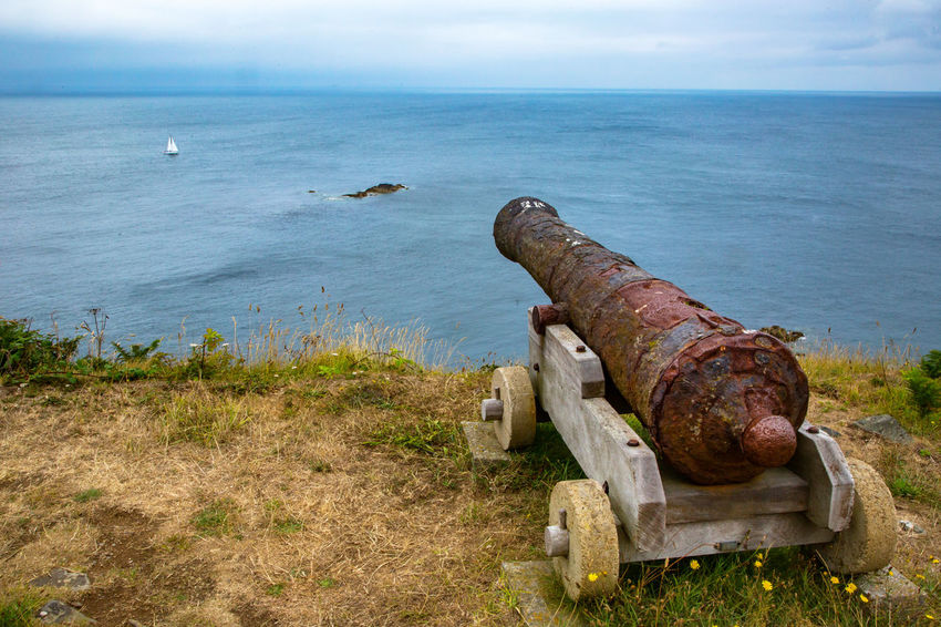 English Channel Eperquerie Isle Of Sark Abandoned Cannon Canon Day Grass History Horizon Over Water Island Military Nature No People Old Outdoors Rusty Sark Sea Sky War Water Weapon