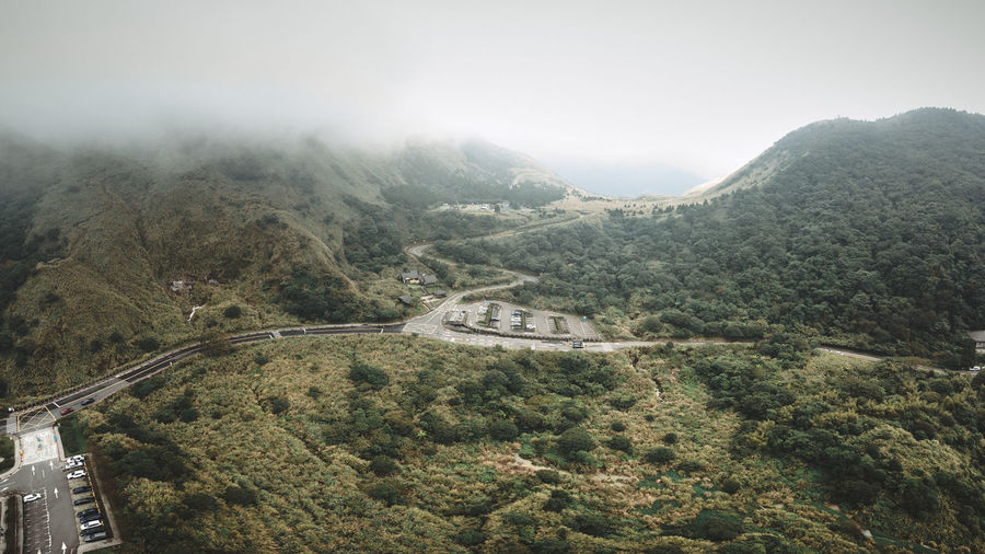 Aerial view of road and parking lot amidst trees against sky