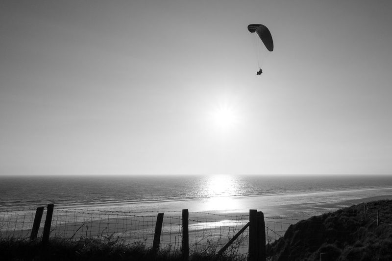 Silhouette person paragliding above sea during sunny day