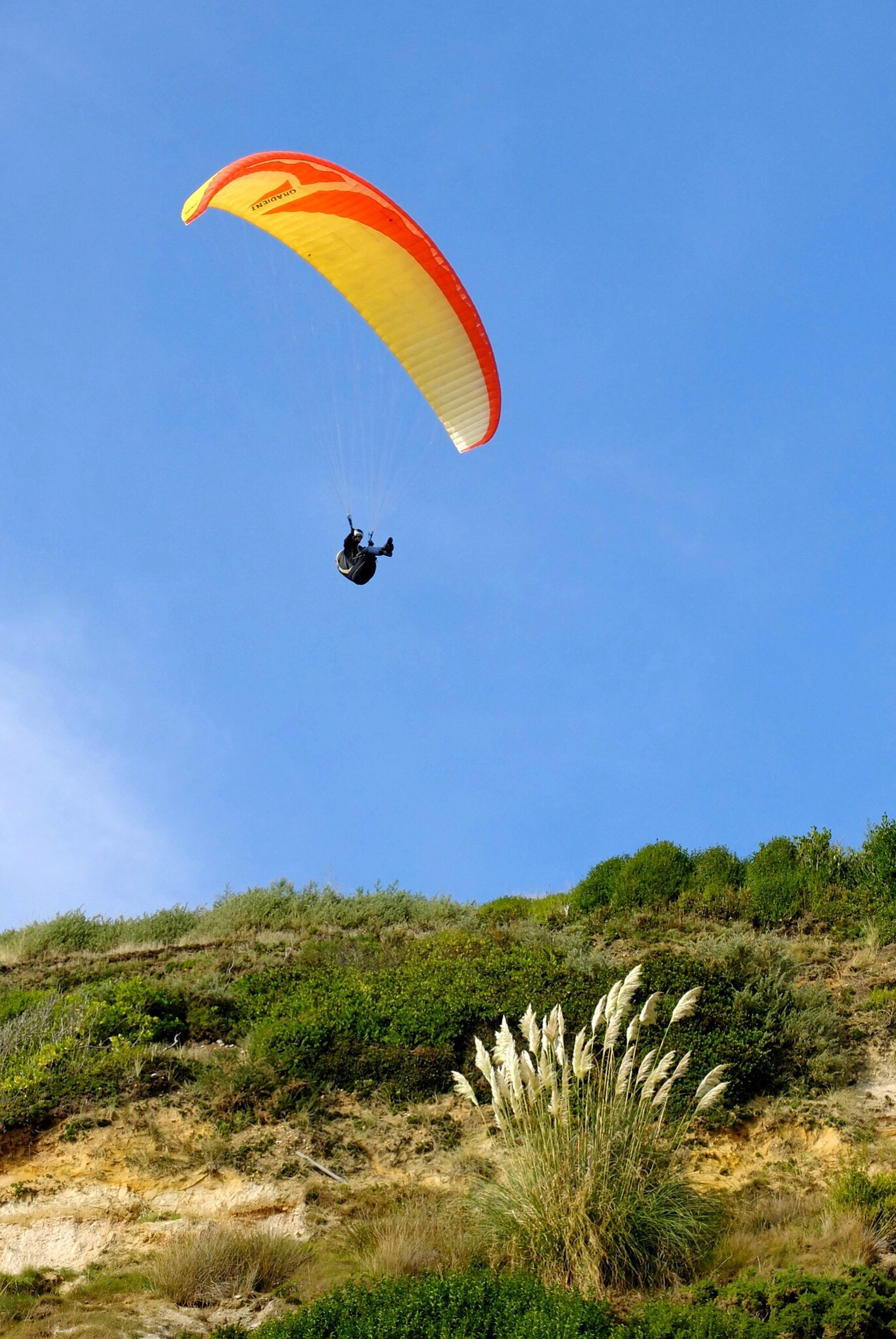 flying, mid-air, parachute, extreme sports, clear sky, transportation, adventure, paragliding, blue, leisure activity, low angle view, exhilaration, copy space, air vehicle, freedom, sport, mode of transport, travel