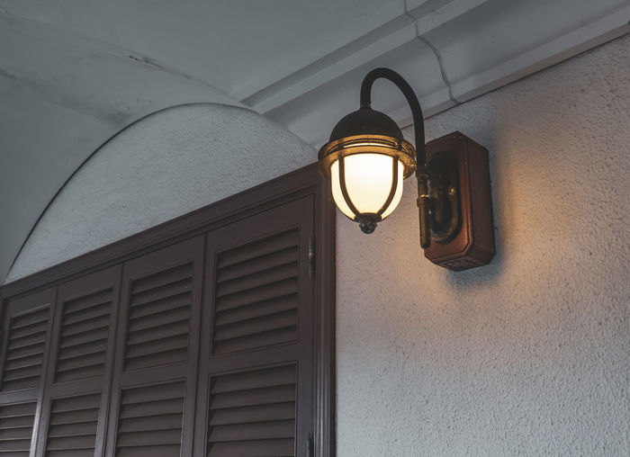 Low angle view of illuminated light bulb hanging on wall of building