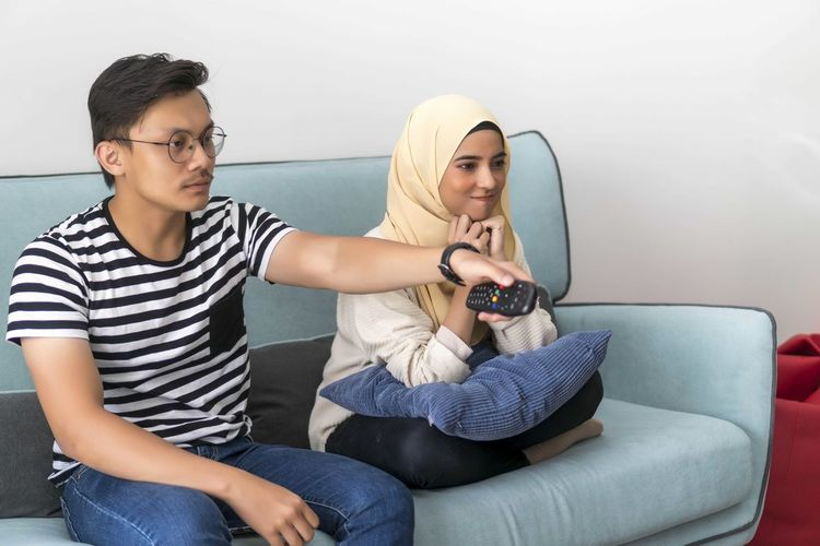 Young Malay Couple at the Sofa watching tv together holding the remote Sitting Casual Clothing Sofa Lifestyles Front View Leisure Activity Three Quarter Length Young Adult Indoors  Technology Real People Young Men Two People Young Women People Men Wireless Technology Furniture Togetherness Communication Teenager Couple - Relationship