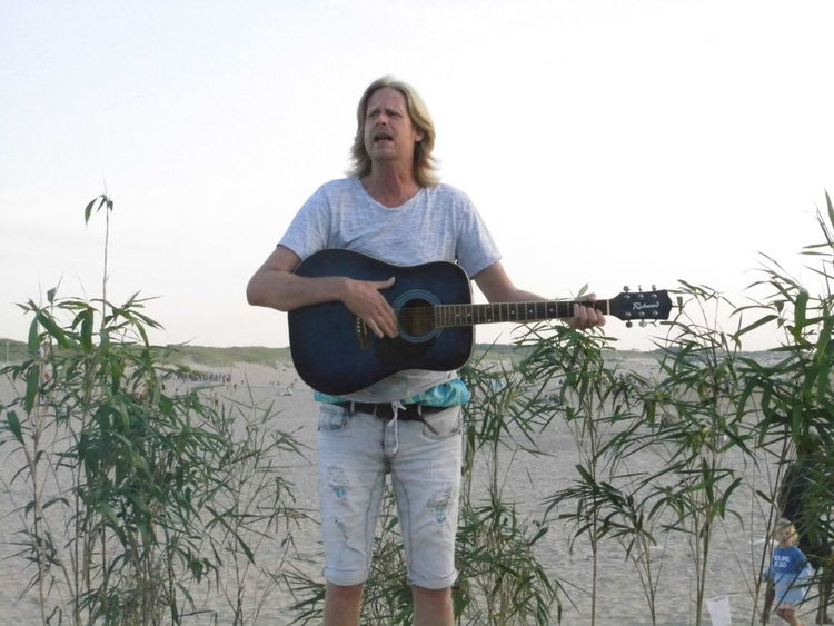 Beachparty Casual Clothing Day Focus On Foreground Front View Guitar Player In Front Of Leisure Activity Lifestyles Music Person Plant Standing Three Quarter Length Vacations Young Adult