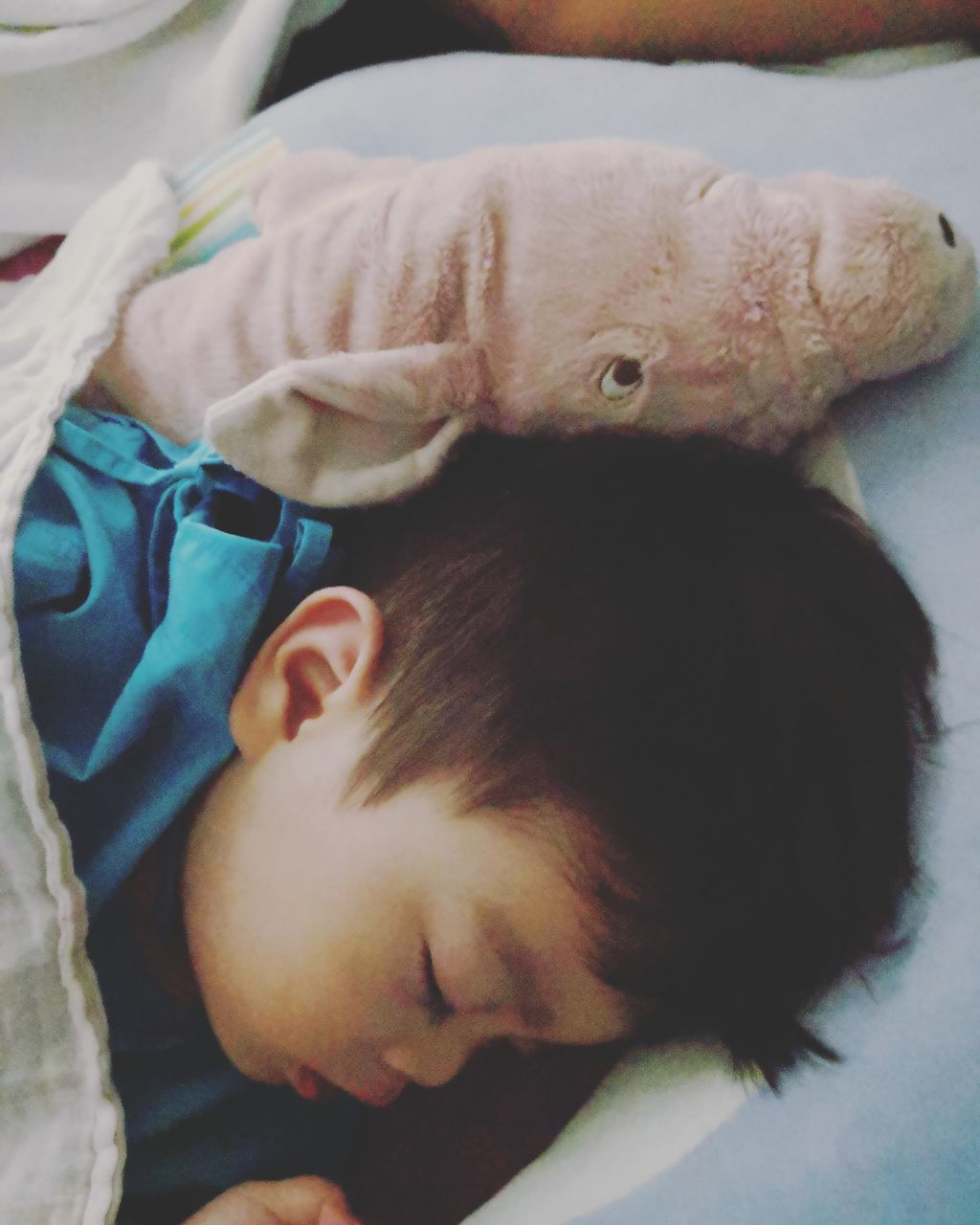 HIGH ANGLE VIEW OF CUTE BABY SLEEPING IN BED