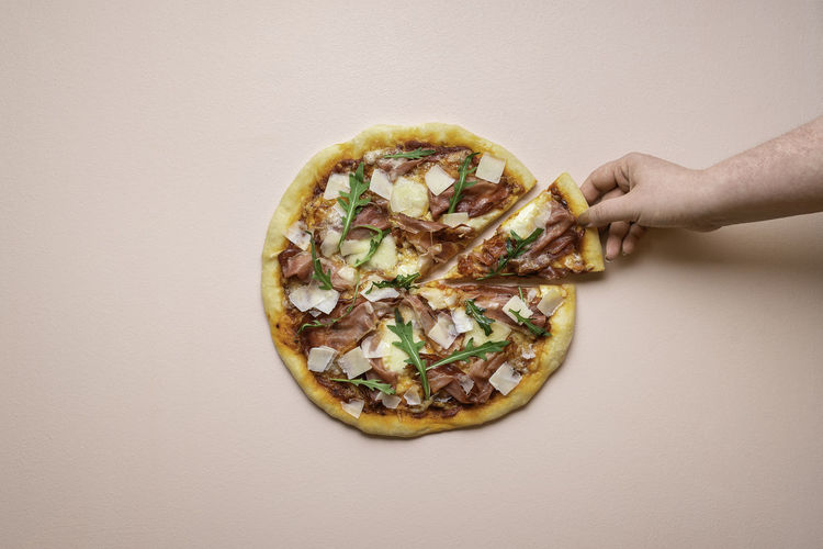 Directly above shot of person holding pizza against white background