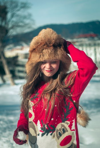 Smiling girl wearing fur hat while standing outdoors