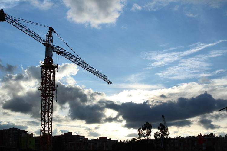 Low angle view of silhouette crane against sky in city