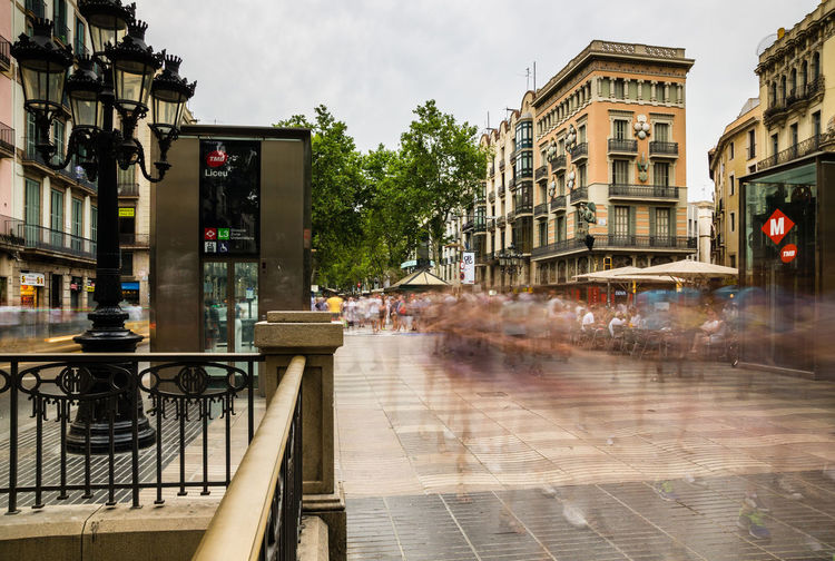 Blurred Motion Of People Walking On Footpath In City