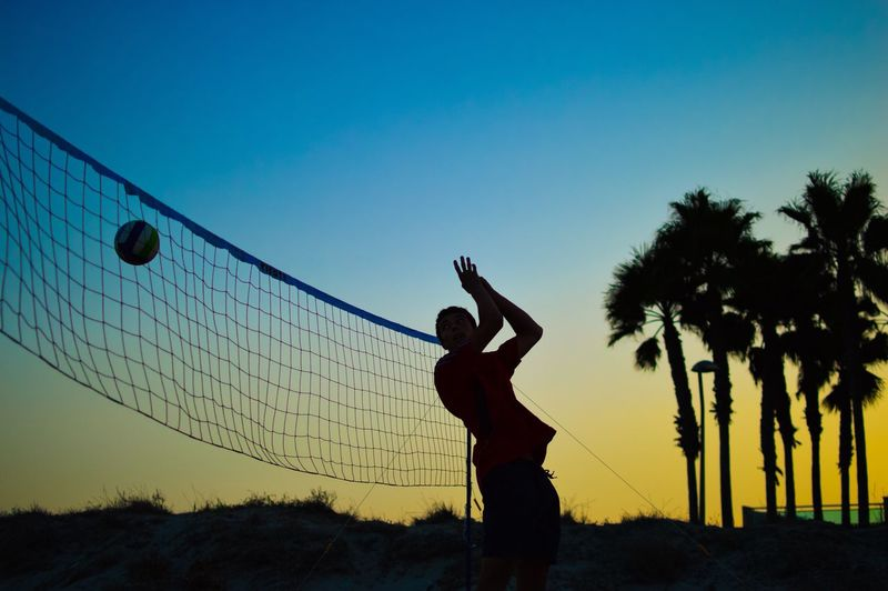 Silhouette man playing volleyball against sky during sunset
