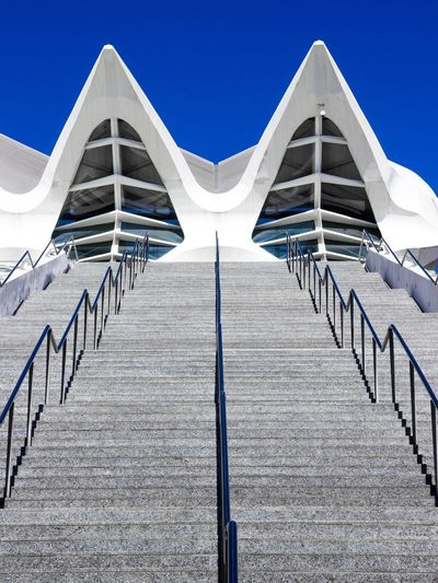 Low angle view of steps leading towards building against clear blue sky