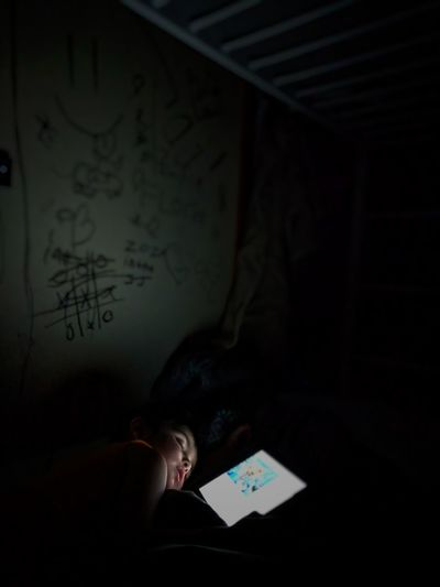 Boy sleeping on bed in darkroom