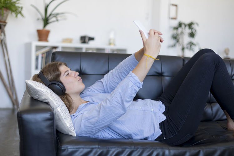 Young Woman Using Phone On Sofa At Home