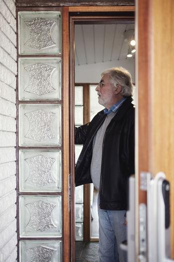 Side view of man standing against door