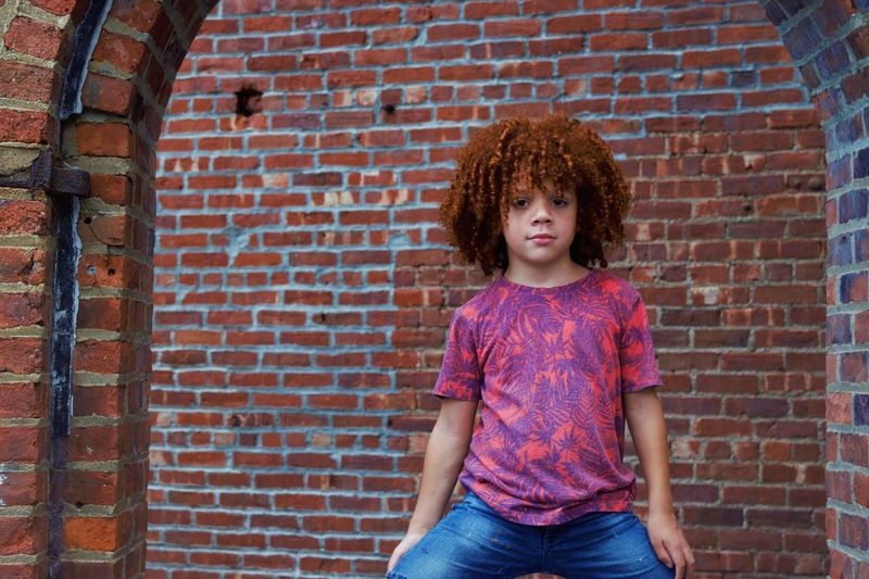 Mixed Race Biracial Redhead Curly Hair Brick Child Brick Wall Childhood Wall Hairstyle Offspring Standing Casual Clothing Front View One Person